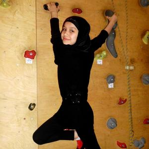 Lächelndes Mädchen mit schwarzem Kopftuch an einer Kletterwand.