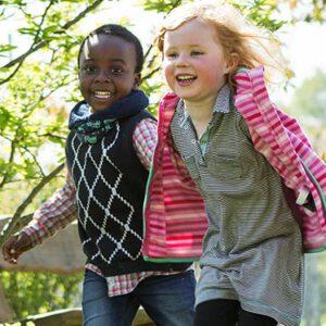 Zwei laufende Kinder unterschiedlicher Hautfarbe.